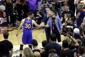 Steph Curry stringe la mano ad un fan dopo aver tirato il suo paradenti durante Gara6 (Foto di Ronald Martinez)