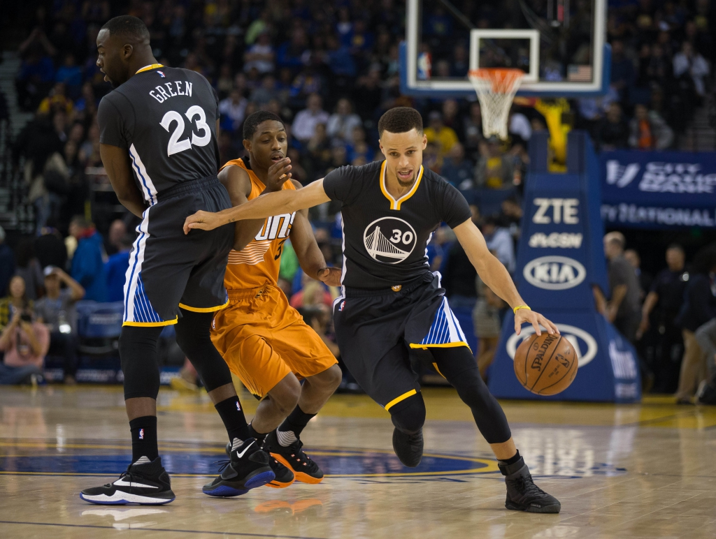 Mar 12, 2016; Oakland, CA, USA; Golden State Warriors guard Stephen Curry (30) dribbles around Phoenix Suns guard Brandon Knight (3) with a screen by Warriors forward Draymond Green (23) during the first quarter at Oracle Arena. Mandatory Credit: Kelley L Cox-USA TODAY Sports